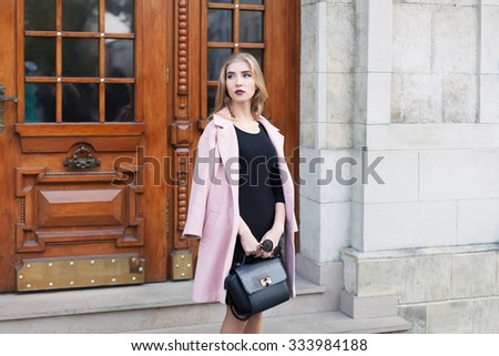 Young beautiful woman standing on the street. Elegant outfit. Full body portrait. Female fashion. - stock photo