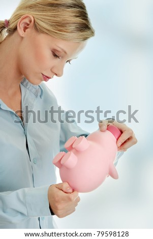 Young beautiful woman standing with piggy bank (money box). - stock photo