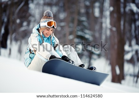 Young beautiful woman strapping on her snowboard at ski slope