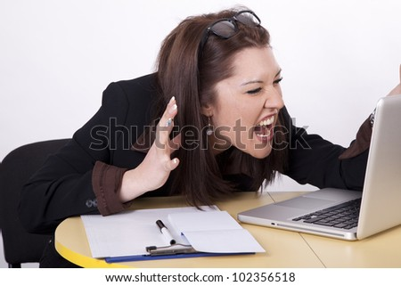 Young beautiful woman stressed yelling at her laptop. - stock photo