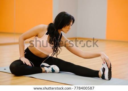 Young beautiful woman stretches in the gym before a workout