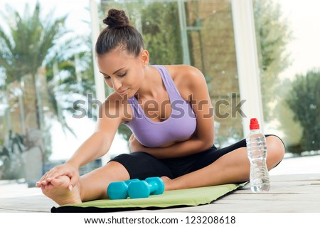 Young Beautiful Woman Stretching Her Leg After Fitness - stock photo
