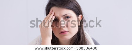 Young beautiful woman suffering from terrible headache. Holding hand on forehead - stock photo