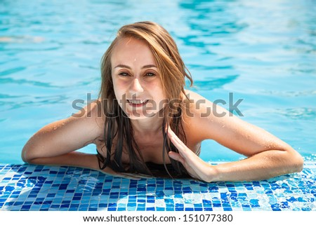 Young beautiful woman sunbathing in the swimming pool - stock photo