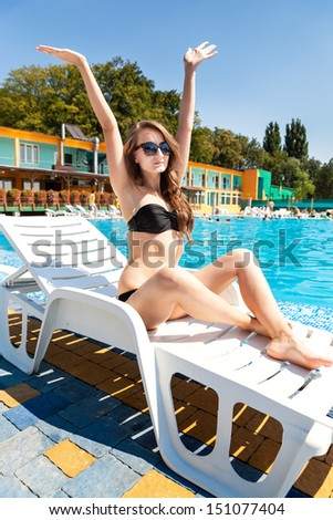 Young beautiful woman sunbathing near the pool holding up hands to the sun - stock photo