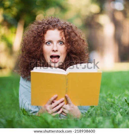Young beautiful woman surprised by the story she is reading in her book.