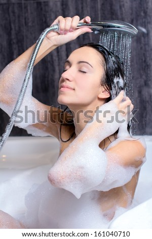 Young beautiful woman taking a bath with foam and washing hair with shampoo - stock photo