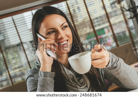 Young beautiful woman talking on the phone in a cafe - stock photo