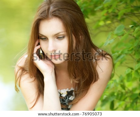 Young beautiful woman talks by mobile phone  near a river - stock photo