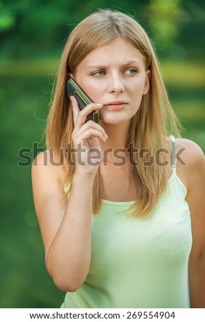 Young beautiful woman talks by mobile phone, on green background. - stock photo
