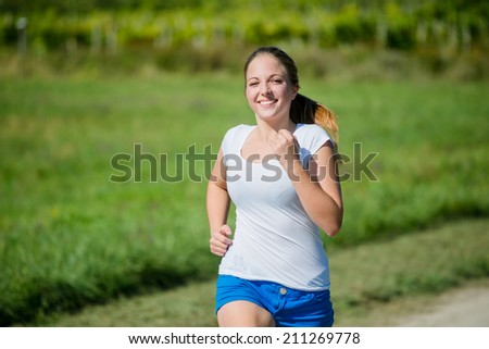 Young beautiful woman (teenager) jogging in nature on sunny day - stock photo
