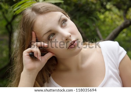 Young beautiful woman thinking and looking up. Face of serious girl on green background of summer park - stock photo