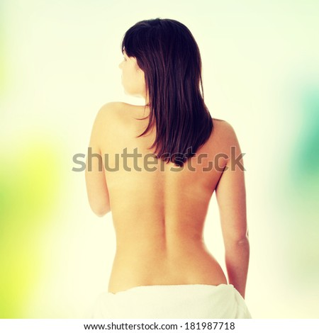 Young beautiful woman topless, in towel, view from back - stock photo