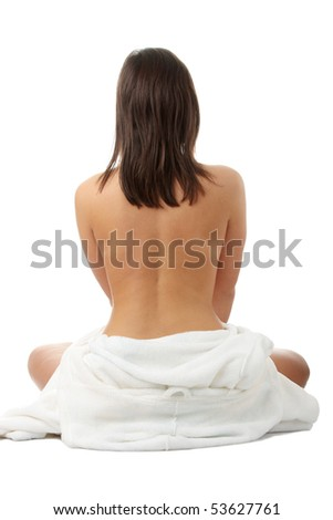 Young beautiful woman topless, in towel, view from back, isolated on white background