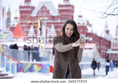 Young beautiful woman tourist taking pictures on mobile phone on the background Red Square, Moscow Kremlin, Russia - stock photo