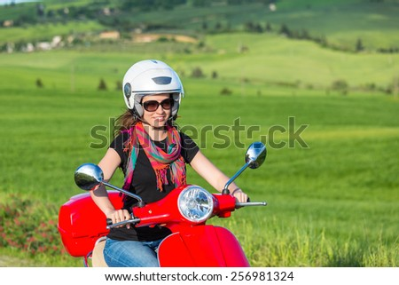 Young beautiful woman traveling by a scooter in tuscany - stock photo