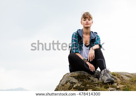 young beautiful woman traveling on mountains with backpack on her back, resting on a rock and and watching the view