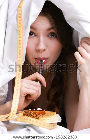 young beautiful woman under white cover eating cake, near - measure - stock photo