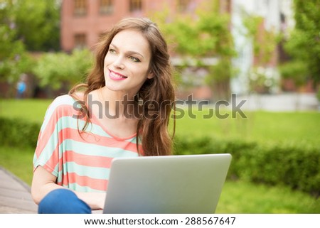 Young beautiful woman using a laptop outdoors