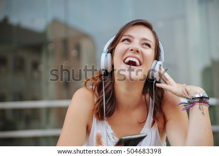 Young Beautiful Woman Using A Smartphone And Listening To Music