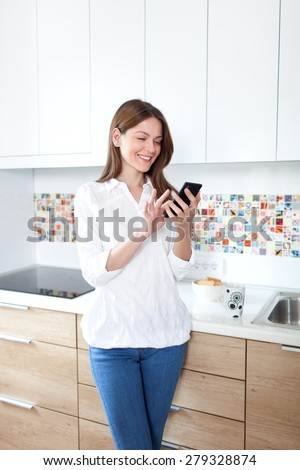 Young beautiful woman using cell phone and having fun in the kitchen - stock photo