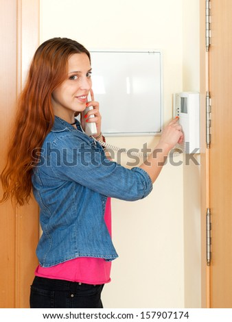 Young beautiful woman using house videophone