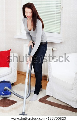 Young beautiful woman using vacuum. Cleaning house conception.