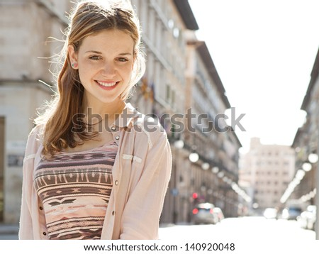 Young beautiful woman visiting a city center during a sunny day, smiling at the camera with buildings in the background. - stock photo