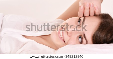 Young beautiful woman waking up in bed