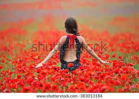 Young beautiful woman walking and dancing through a poppy field, summer outdoor.   - stock photo