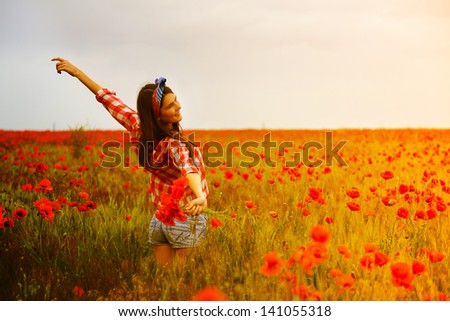 Young beautiful woman walking and dancing through a poppy field, summer outdoor. Toned. - stock photo