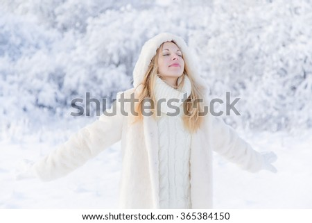 Young beautiful woman walking in a park and breathing fresh winter air and feeling wonderful - stock photo
