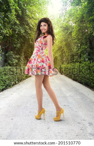 Young beautiful woman walking in a park path - stock photo