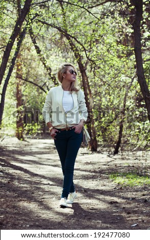 young beautiful woman walking  in park - stock photo