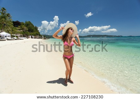 Young beautiful woman walking on the beach - stock photo