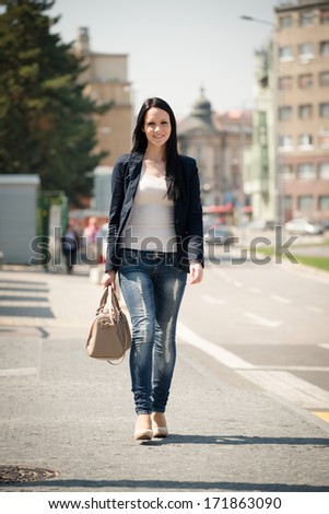 Young beautiful woman walking street on sunny day with handbag