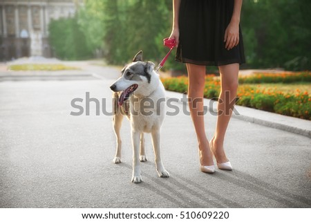 Young beautiful woman walking with dog outside