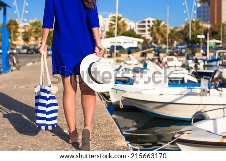 Young beautiful woman walking with hat and bag on dock near the boat - stock photo