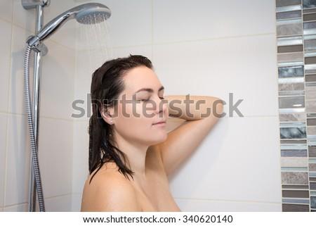 young beautiful woman washing her hair in shower - stock photo