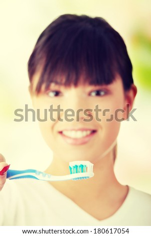 Young beautiful woman washing her teeth with blue brush - focus on brush