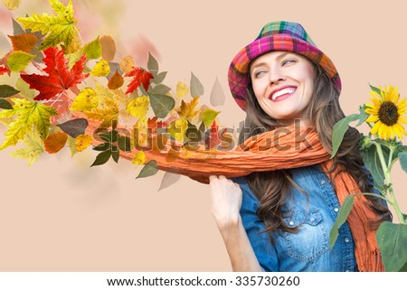 Young beautiful woman wearing autumn clothing holding autumn flowers. Beautiful autumn woman with scarf and flying away colorful leaves - stock photo