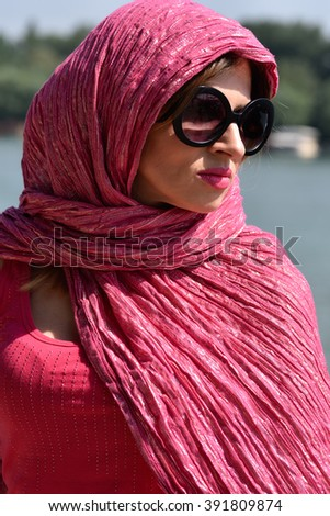 young beautiful  woman wearing big sun glasses and pink scarf around her head relaxing outside blurred water background  - stock photo