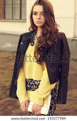 young beautiful woman wearing dress, yellow pullover and leather jacket posing outdoors. stylish fashion portrait - stock photo