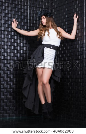 Young beautiful woman wearing fashionable clothes posing in the studio