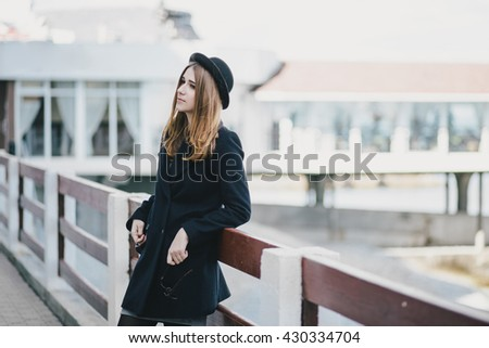 Young beautiful woman wearing hat and coat standing on the embankment near sea - stock photo