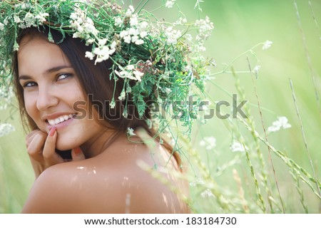 Young beautiful woman wearing herbal wreath enjoying in green spring field - stock photo