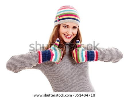Young beautiful woman wearing warm autumn clothes - colorful hat and mittens, grey sweater - showing thumb up gesture with both hands and smiling isolated on white background - say no to cold and flu