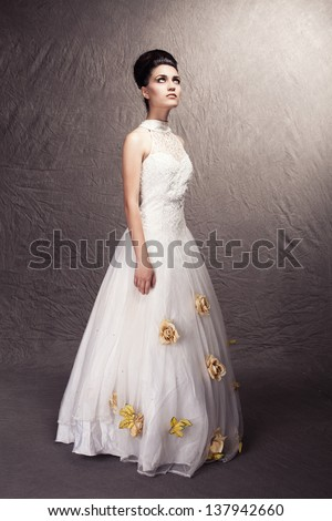 young beautiful woman wearing wedding dress with flowers standing on grunge background - stock photo
