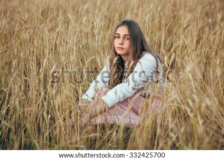 Young beautiful woman wearing white  and pink dress sitting in wheat field - stock photo