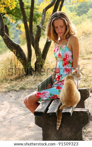Young beautiful woman with a book in hand and a cat sitting on the bench against a background of green sunlit nature - stock photo